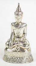A white metal filled figure of seated Buddha on a