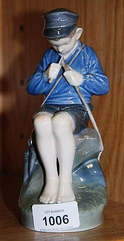 Royal Copenhagen figurine of a young boy fixing a