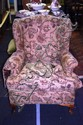 A vintage, wingback armchair with tapestry