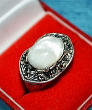Silver ring set with oval shell setting