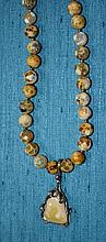 A strand of agate beads with central pendant of