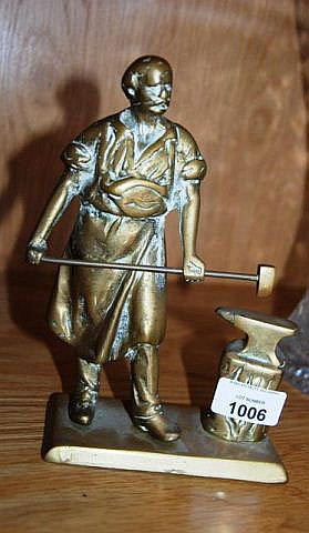 An old cast brass figure of a blacksmith with