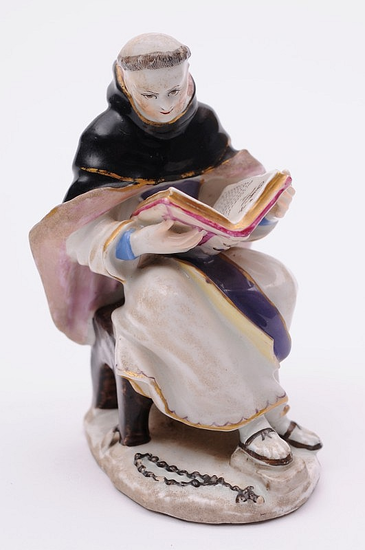 A Bow figure of a monk wearing a black and pink