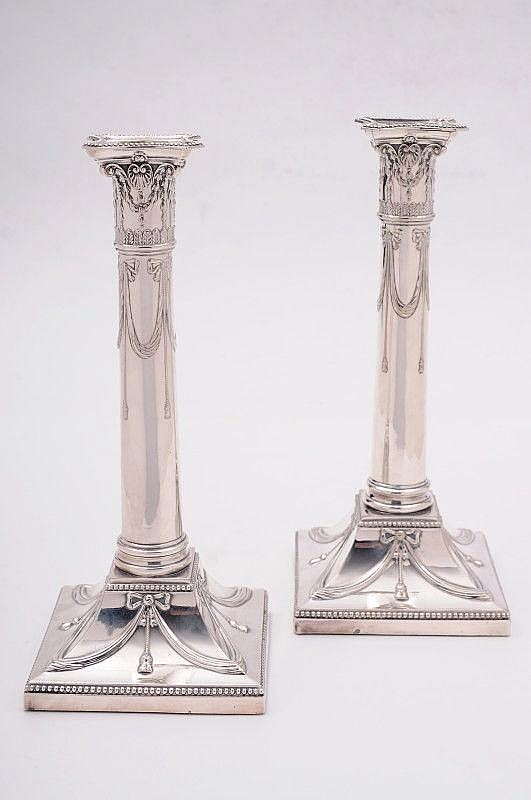A pair of plated candlesticks, with beaded sconces