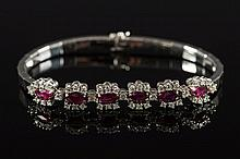 An 18ct white gold, ruby and diamond bracelet: comprising six ruby and diamond clusters, approximately 19.5gms gross weight.