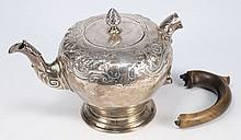 A George II silver teapot maker HB, London, 1746: crested, of pear-shaped outline, with foliate and scroll decoration, on a spreading circular foot, w