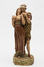 A Royal Dux porcelain group of young Grecian lovers: decorated in green and brown matt glazes enriched with gilding, the girl wearing flowing skirts,