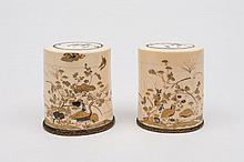 A pair of Japanese shibayama decorated ivory pots and covers: decorated with birds, butterflies and insects amongst flowering shrubs, mounted on polis