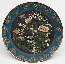 A large Chinese cloisonne charger: decorated with birds amongst flowering shrubs and plants, 61cm. diameter.
