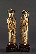 A pair of 19th century Chinese carved ivory figures: of a mandarin and his wife, both in traditional costume, raised on polished wood bases, each 30cm