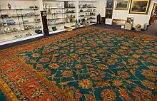 A Turkish carpet of very large size:, the blue/green field with an all over geometric design of interlaced serated palmettes and lanceolate leaves in