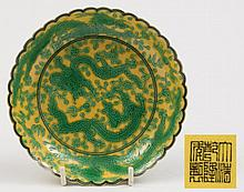 A Chinese green enamelled yellow ground 'dragon' dish: with scalloped black lined rim, painted and incised with sinuous five-clawed dragons in pursuit