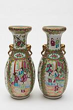 A pair of Cantonese porcelain vases: of oviform with in scrolling rims and elephant mask handles, enamelled with alternating panels of figures in pavi