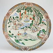 A Chinese famille verte dish: the centre decorated with figures by a pavilion in an extensive lake landscape, the rim with key and diaper pattern band