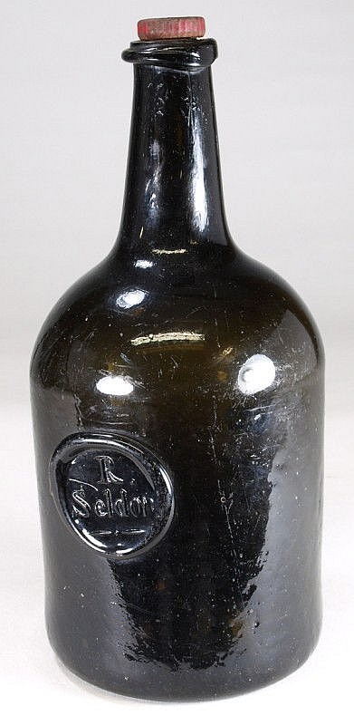 A sealed wine bottle of squat cylinder form with
