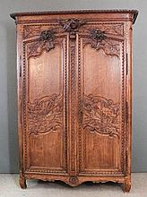 A late 18th/early 19th Century French Provincial panelled oak armoire with moulded overhanging cornice