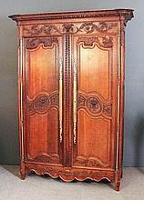 An 18th Century French Provincial panelled oak armoire (from the Normandy region) region with heavy carved and moulded cornice