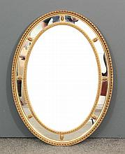 A gilt framed oval wall mirror of 18th Century