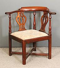 A George III mahogany corner armchair, the