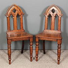 A pair of Victorian oak hall chairs with pierced