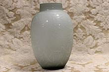 A large art glass vase with leaf decoration.