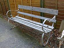 Late 20th Century slatted garden bench having cast iron ends
