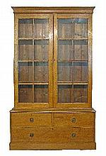 19th Century pine sided oak two section library bookcase, the upper section fitted four shelves enclosed by a pair of glazed doors, the base having a