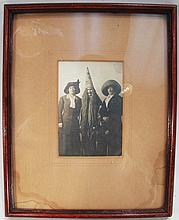EARLY 20TH CENTURY PHOTOGRAPH OF THREE WOMEN.  One of which is dressed like a witch or sorcerer in wooden frame.