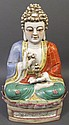CHINESE BUDDAH FIGURE.  Seated in a lotus flower on a plinth.  Polychrome porcelain.  16 1/2