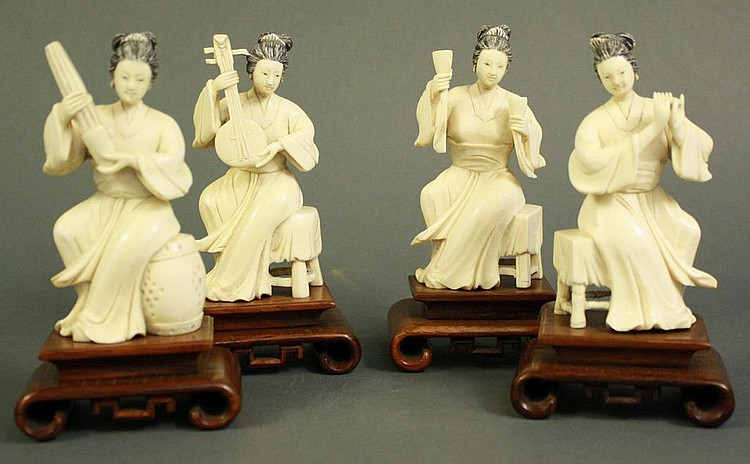 FOUR CHINESE CARVED IVORY FIGURES ON ROSEWOOD