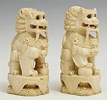 Pair of Chinese Carved Ivory Foo Lions, early 20th c., signed on the bottoms, on carved wooden stands, H.- 4 1/8 in., W.- 1 11/16 in...