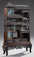 Oriental Carved Hardwood Etagere-Parlor Cabinet, early 20th c., a peaked roof style crown over a cupboard door and multiple open she...