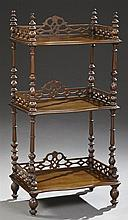 Victorian Classical Carved Mahogany Etagere, c. 1900, crowned by turned finials joining a pierced three-quarter gallery, surrounding...