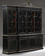 Hollywood Regency Parcel Gilt Ebonized Oak Breakfront Bookcase, c. 1930, in the style of Dorothy Draper, the broken arch crown over...
