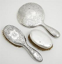 Group of Three Sterling Items, early 20th c., consisting of a clothes brush, a hairbrush by Gorham, with relief floral decoration, a...