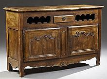 Unusual French Provincial Louis XV Style Carved Walnut Sideboard, c. 1815-1830, the stepped edge top over a central drawer, flanked...