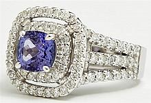 Lady's 14K White Gold Dinner Ring, with a cushion cut 1.63 carat tanzanite atop a border of round diamonds and a pierced concentric...