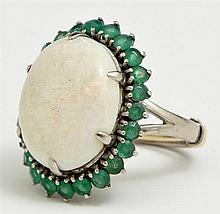 Lady's 14K White Gold Dinner Ring, with a cabochon oval approx. 13 carat opal atop a frame of round emeralds.