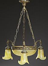 French Art Glass and Bronze Four Light Chandelier, c. 1920, with a central yellow large art glass bowl with a light within, in a gil...