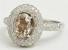 Lady's 14K White Gold Dinner Ring, with a 2.05 carat oval cognac diamond within three concentric rows of small diamonds, each side o..