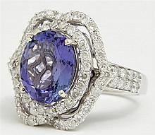 Lady's 14K White Gold Dinner Ring, with an oval 4.89 carat tanzanite within a border of small round diamonds and an outer chevron bo..