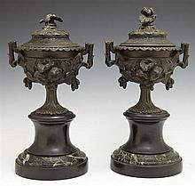 Pair of Diminutive Patinated Spelter Mantel Garnitures, 20th c., in the form of lidded urns with relief floral decoration, on socle...