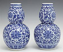 Pair of Chinese Porcelain Double Gourd Vases, early 20th c., with blue and white floral decoration, the underside signed within a do...