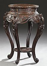 Chinese Export Highly Carved Hardwood Pedestal Table, early 20th c., the Greek key and beaded edge circular top, over a bombe pierce...