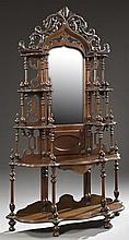 American Victorian Carved Walnut Etagere, c. 1890, the pierced carved foliate crown over a Gothic Style lancet shaped mirror, flanke...