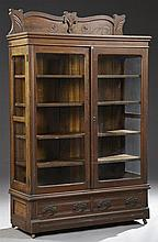American Eastlake Carved Mahogany and Oak Bookcase, c. 1900, the arched crest above a stepped crown over double glazed doors, flanke...