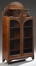 American Art Nouveau Carved Mahogany Bookcase, c. 1900, the oval shaped back with foliate decoration over an open shelf, above doubl...