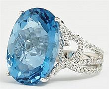 Lady's 18K White Gold Dinner Ring, with a 24.68 carat oval blue topaz, within a swirled mount with round diamonds, the triple split...