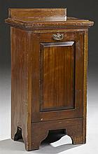 English Carved Mahogany Coal Hod, c. 1900, the tablet crest over a stepped edge top, to a fielded panel fall front door, opening to...