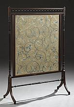 English Carved Mahogany Fire Screen, c. 1900, with a spindled top over a floral embroidered panel, flanked by turned supports, to a...